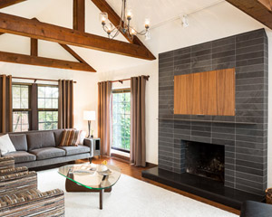 One element that required a complete overhaul was the living room fireplace.  The out-sized brick is now gone, replaced with black slate, and a raised, honed hearth in absolute black granite.  The same quartered walnut cabinets are used to cover a concealed television above the fireplace, with a rolled steel frame.