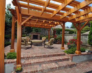 And what a backyard it is.  Twin cedar arbors define brick-lined patios that lead to a romantic outdoor fireplace.  The warm colors of the cedar and brick compliment the deep brown newly painted home, with pops of color from the trees, bushes and plants surrounding it.