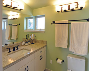 The bathroom is placed squarely in the corner of the new dormer, where it benefits from windows and bright interior colors. It includes a custom vanity and Pental cappuccino counters.