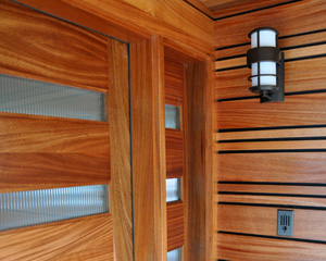 Linear art crafted from mahogany. The alternating widths provide visual interest and tie in with the horizontal sidelite and door panels. Reeded glass lets in light and maintains privacy.