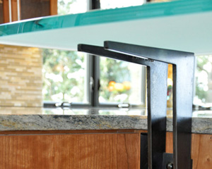 The bar counter supports are custom made from blackened steel.  Three of them hold up the curved 3/4 inch etched glass counter.  The same steel is used in other locations through the home.