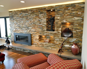 The floating hearth is cast concrete and the surround is quartzite, with puc-lit niches.  The hearth is engineered to double as a seating area while entertaining, and tape light along the top edge of the quartzite surround illuminates the ceiling.