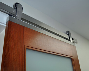 A custom built stainless piece at the top of the door connects the factory hardware to the door.