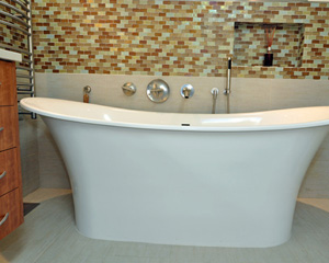 Where a dated vanity once stood there is now an elegant Victoria + Albert soaking tub with a niche and hand-held faucet.