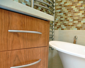 The heated towel bar to the left is on a timer and shows off nicely against the tile and warm wood tones.