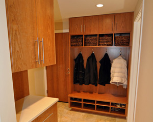 Outside the powder bath, a new mudroom cabinet is both beautiful and functional, with cubbies built to fit the baskets.  The door was originally not slated 	for replacement, but then added to keep materials and wood tones consistent.