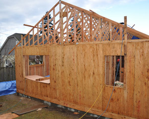 The addition takes shape as trusses are installed by custom home builder seattle.