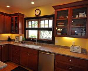 Custom cherry cabinets are stained a deep red, reflecting the warm, rich paint colors throughout the home.