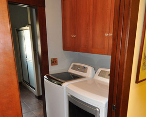 Just off the kitchen is the new laundry room, with washer/dryer on one side, and a convenient storage cabinet and folding counter on the other.