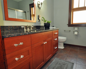 The master bathroom has the same custom cherry cabinets as the kitchen.  The cabinetmaker also fabricated the mirror frame, so all the wood and stain is consistent.  Warm colors continue with the floor tile.
