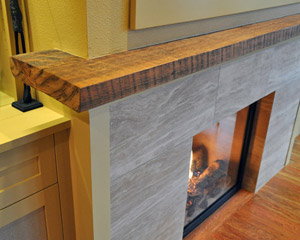 The mantle was the only thing saved from the original fireplace--a slab of wood that had been salvaged from a local historic building many years ago. The ends required cuts, so our carpenters artistically reproduced the colors of the rest of the slab on the cut ends.