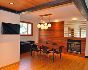 That boring dining room is no more. �The horizontal cedar and fir on the fireplace wall warm up the room, and integrate the two-sided fireplace into the room.