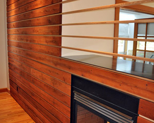 The natural wood is inset into a sheetrock frame to the left, and the VG fir extends through the fireplace opening, creating a clear delineation between the dining and living areas without blocking light.
