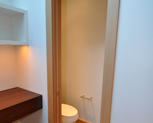 The powder room is conveniently tucked away with a laminated glass pocket door.