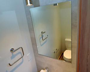 A small sink and mirror is tucked into the other side on a wall clad with marble subway tile.