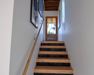 The stairs to the lower level are made from glu-lams, with stained wood risers.   The space below hides the water heater.  Each floor has a single Convectaire unit for heat, which keeps the rooms as toasty as they need to be
