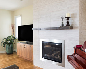 The living room also features a gas fireplace with Statements Velvet II large-format tile and a reclaimed wood mantle, a rustic counterpoint to the clean lines of the fireplace and adjacent cabinets.