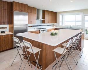 The island is also in walnut, with quartz Pental Lattice countertops to match, and installed in a waterfall style at the raised counter.