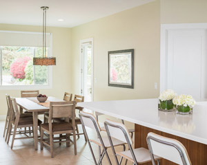 The dining room is just adjacent, and features a big window out into the front yard and access to the side yard.  The selection of a beachy light-colored wood table and chairs is just perfect.