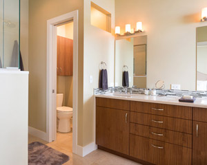 The ensuite master bath is spacious and private, with a separate toilet room, a roomy shower and the same walnut cabinets as the kitchen.