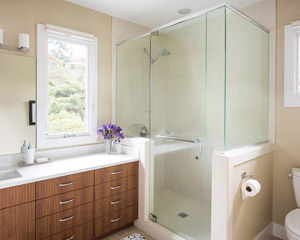 A walk-in closet divides the suite, and on the other side, a spacious bath with walnut cabinets and a shower with custom glass.