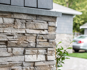 Siding is specially painted James Hardie shingles installed randomly for a beachy look, with blue stone sills as a belly band between the shingles and stacked stone.  The blue stone also serves as the sill for all of the windows.