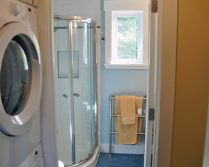 Directly adjacent to the bedroom are the laundry and bath areas.  A stacking washer/dryer fits neatly into the alcove, with a closet on the opposite side and a pocket door to close it off for noise.