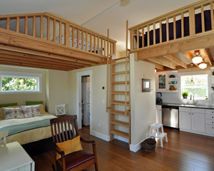 Nearly all of the main floor ceilings are made from exposed tongue and groove fir, which  serves as the flooring for the loft above.  From this level, it's clear that loft access is via the ladder, but how?