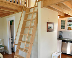 The ladder was designed and custom built to lift and pull out a few feet so that it's stable and easier to climb.  A matching wood railing keeps the edges of the loft safe.