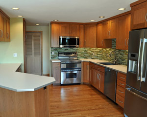 The new cherry cabinets with extra-wide shaker rails bring a deep wood glow to the remodeled kitchen.  They were selected with budget in mind but constructed with plywood boxes for longevity.