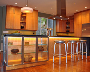 The island is long enough that it includes the display case and ample room for seating.    The waterfall counter installation to the right of the seating area encloses that space, and under-cabinet lighting illuminates both areas.