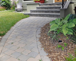 A concrete walk was removed to install a new curving paver pathway to the front door, the width of the new front porch.